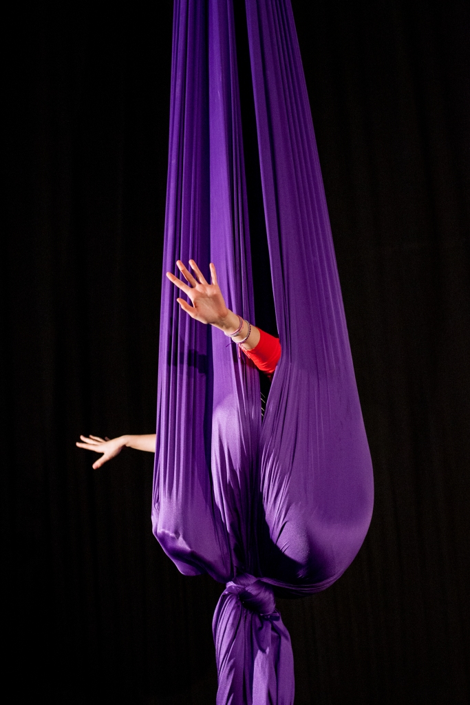 Two white hands peek out from a purple cocoon of aerial fabric.
