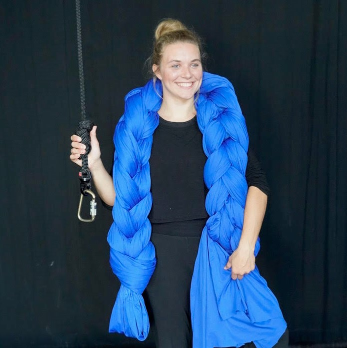 A young white woman stands smiling with a large braid of blue fabric draped over her shoulders. In one hand she holds a sturdy black rope with a carabiner tied to one end.
