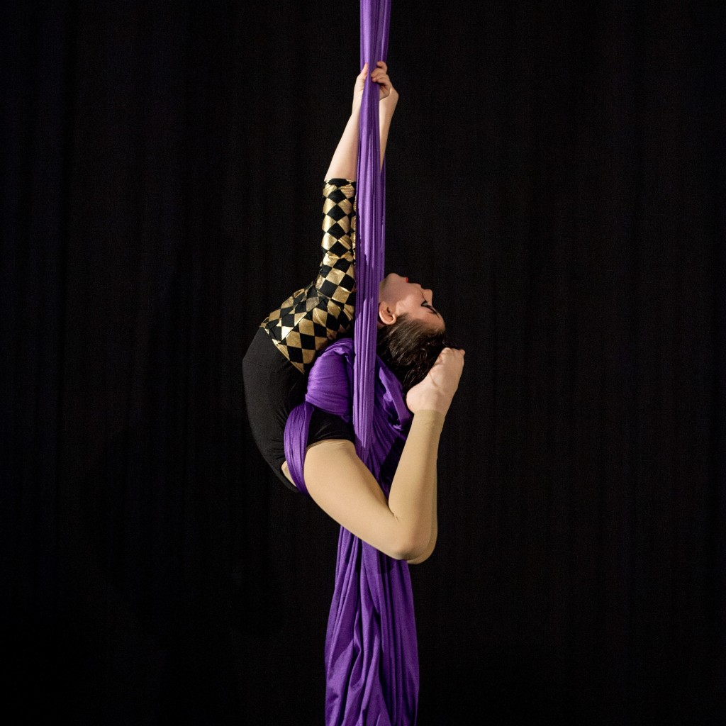A young white child puts their toes to their head while suspended on purple aerial fabric.