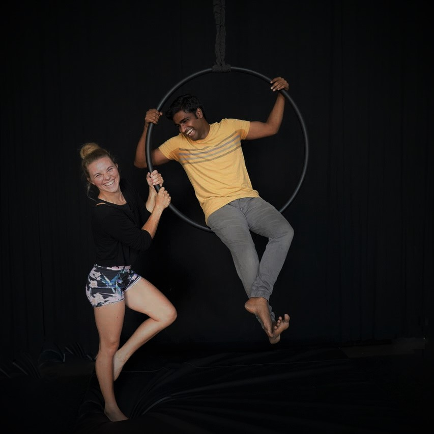 A young brown man is sitting on an aerial hoop. A young white woman hangs on to the side of the hoop. They both appear to be having the time of their lives.
