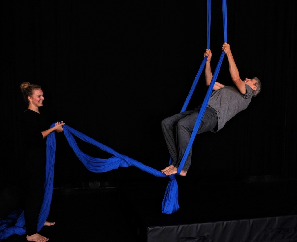 A young white woman holds the ends of blue aerial fabric as an older white person swings on the fabric.