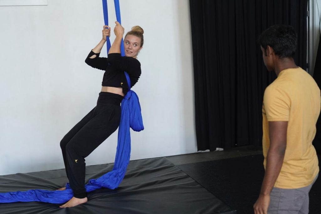 A young white woman leans backwards into blue aerial fabric as if demonstrating a skill. A brown man watches her as she teaches.