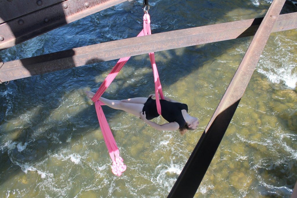 A young white woman hangs suspended over a rushing river on two pieces of pink aerial fabric. Despite the chaos of the water, she appears relaxed.