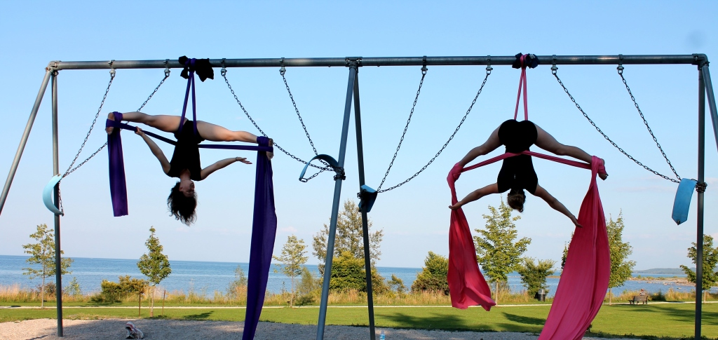 Two white teenage girls hang upside down on fabric draped over a swingset.