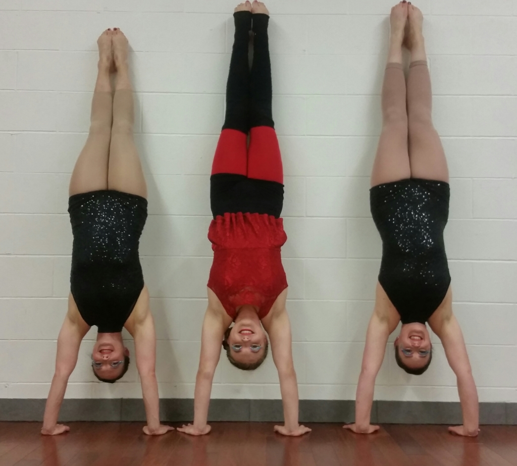 Three white women are smiling doing handstands against a wall. Two of the women are wearing black sparkly biketards with nude tights and bare feet. The midle woman is wearing a costume with a bright red top and leggings,overlayed with black shorts and legwarmers that cover her knees.