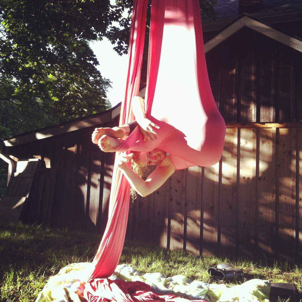 A young white woman peeks out from within a hammock of pink aerial fabric. She looks happy. Behind her is a shed, the photo appears to be taken in a backyard. Underneath her there is nothing but a blanket.