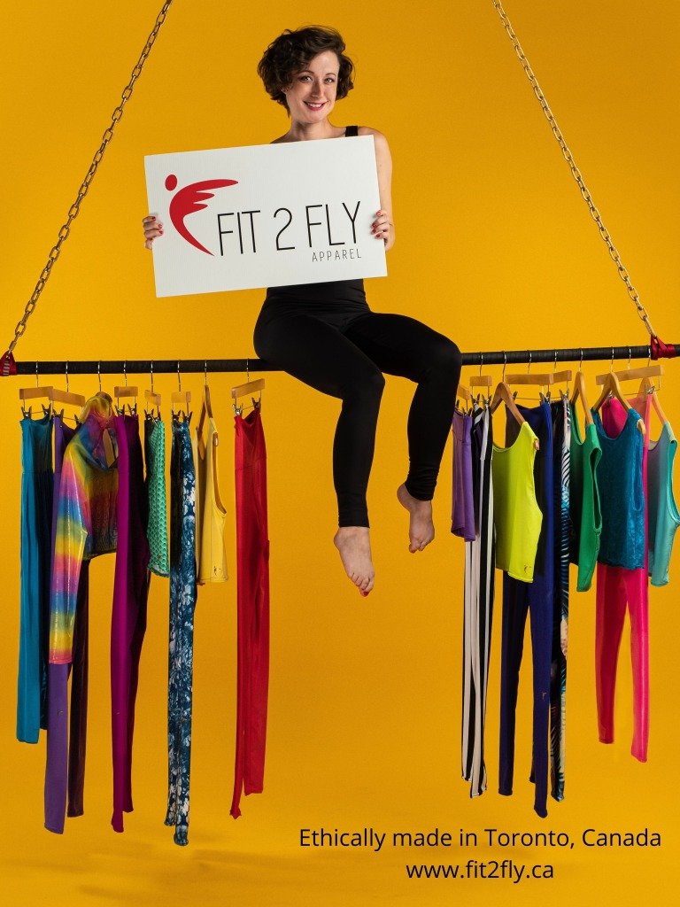 """A young white woman sits on top of a suspended metal bar against a yellow background. She is holding a sign that reads Fit 2 Fly Apparel"""". Below her, an assortment of colourful leggings and tops are hanging off the bottom of the bar."""