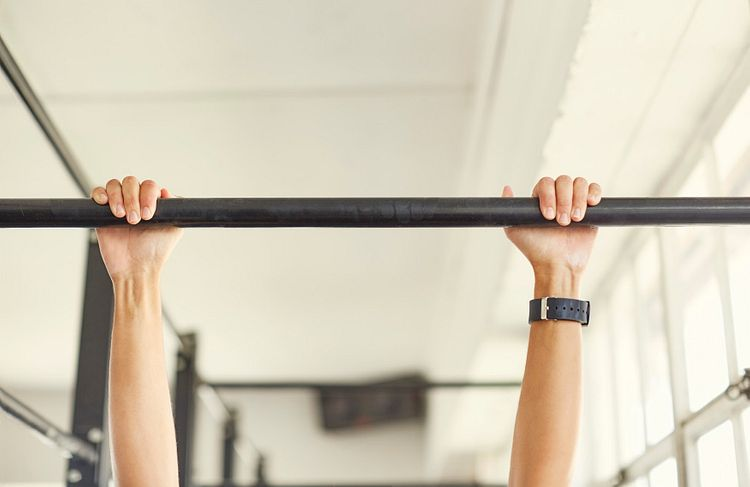 Feminine white hands and wrists grip a black pullup bar as if hanging from it.