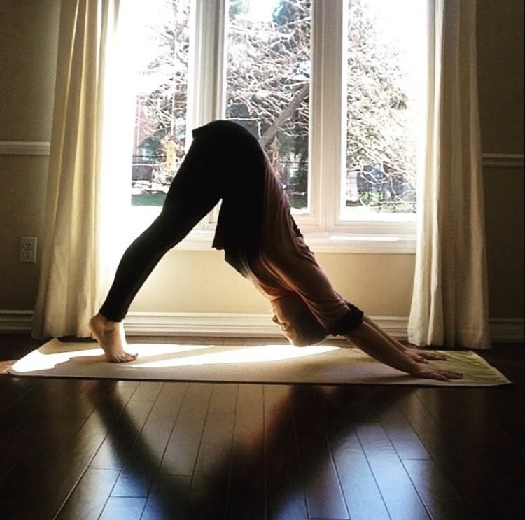 A young white woman does a downward dog position in a sunny room.