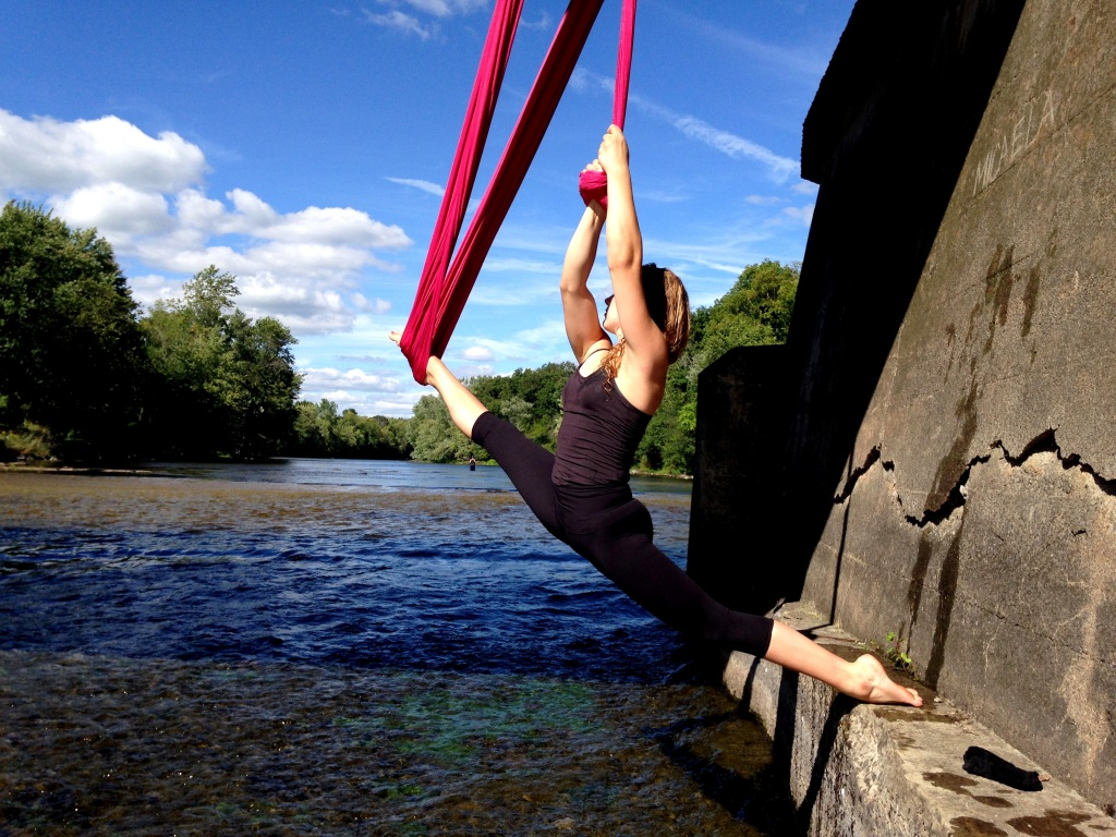 A young white woman hangs on pink aerial fabric over a calm stream. She is looking into the distance.