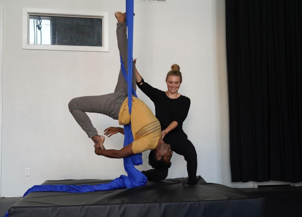A young white woman, supports a young brown man as he hangs upside down on blue aerial fabric. Both people are smiling.