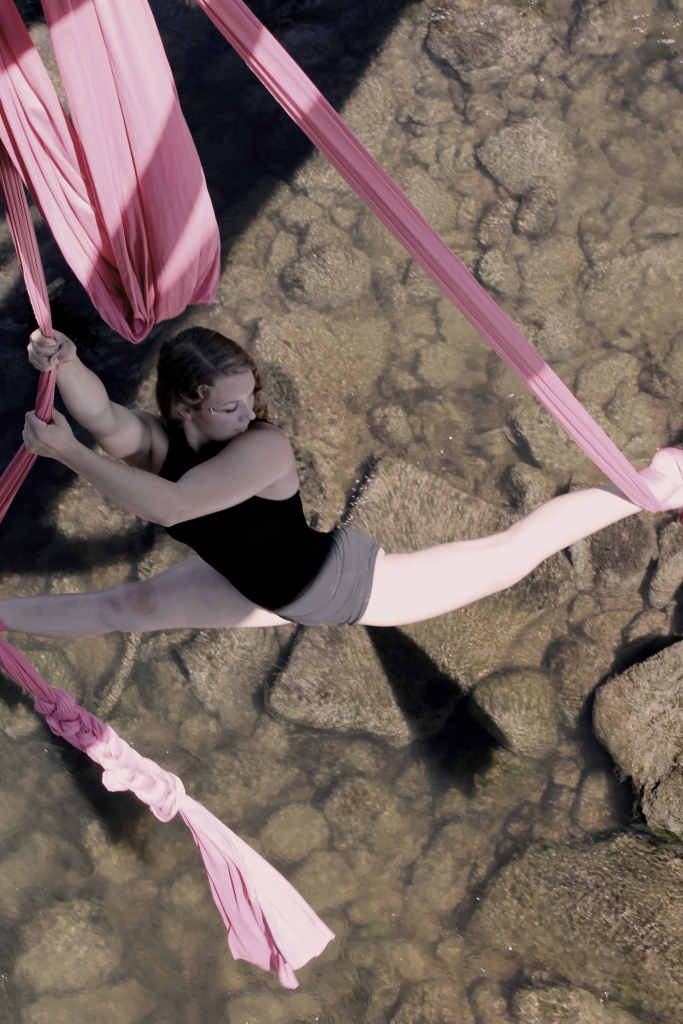 A young white woman is suspended over a calm river hanging off of two pink pieces of aerial fabric.