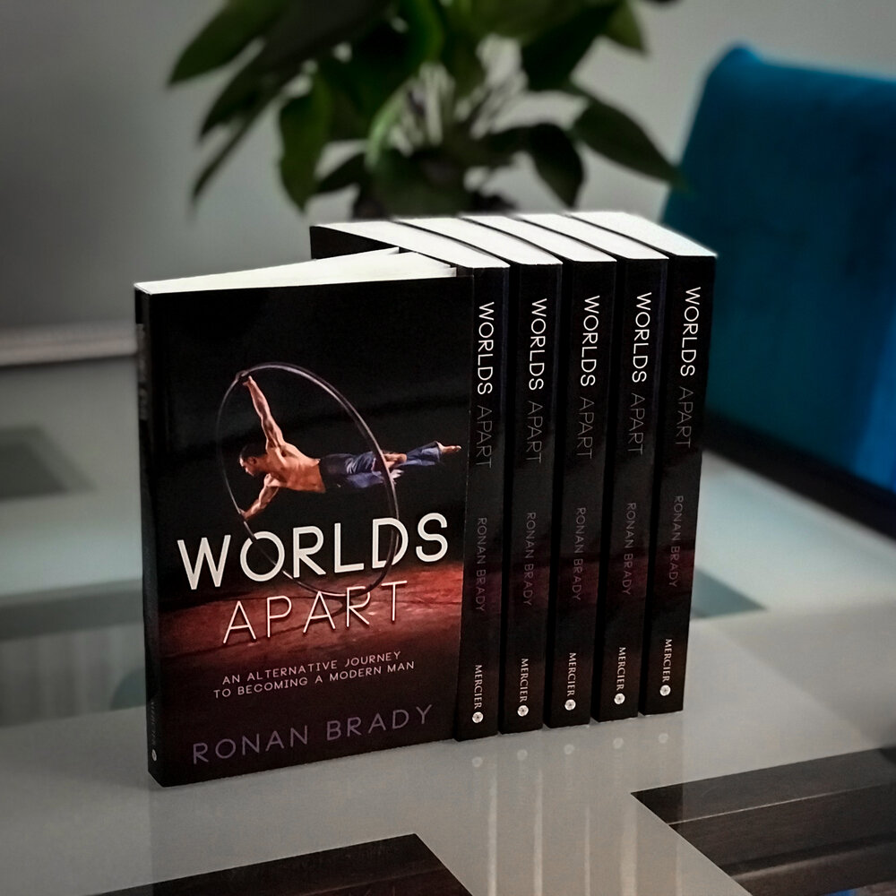 """A stack of books stands upright on a shiny table. The front cover is black and sleek with white text reading """"Worlds Apart: an alternative journey to becoming a modern man. By Ronan Brady."""" Behind the text a muscular white man in only blue jeans spins on a large metal ring known as a Cyr wheel."""